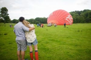 2 people hugging while watching a hot air balloon inflate