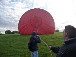 man inflates hot air balloon