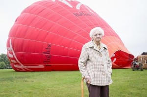100 year old stands by hot air balloon